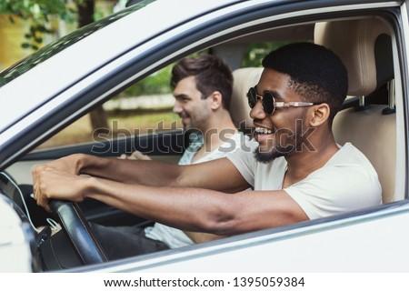 Happy millenials friends traveling by car, having fun