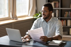 Happy millennial african american businessman in eyewear holding documents, doing paperwork, preparing report or analyzing market research results, working on computer in modern workplace office.