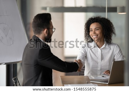 Happy millennial african American businesswoman shake hand greeting or get acquainted with male colleague, smiling biracial woman employee handshake man partner, closing deal at negotiations