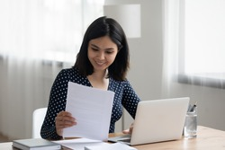 Happy millennial Asian girl sit at desk work on laptop consider read good news in post paper correspondence or letter document, smiling Vietnamese young woman study on computer prepare report
