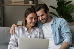 Happy millennial Caucasian couple look at laptop screen watching movie or video online on gadget. Smiling young man and woman spouses use modern computer, relaxing on couch at home together.