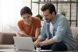 Happy millennial Caucasian couple sit on couch at home look at laptop screen shopping online together, smiling man and woman browse internet pay bills on internet on computer, use modern gadget
