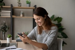 Happy millennial Caucasian female sit at desk at home have fun texting messaging on modern smartphone gadget, smiling young woman laugh watching funny video on cellphone, use technology on cell