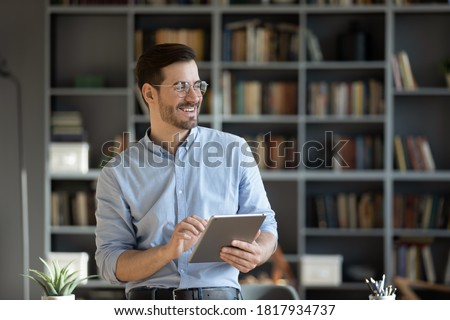 Happy millennial Caucasian man in glasses use tablet look in distance planning or visualizing future success. Smiling young male work on pad gadget, dreaming or thinking. Business vision concept. Foto stock ©