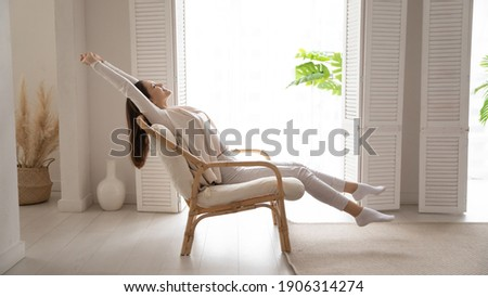 Happy millennial Caucasian woman sit in cozy chair in design home stretch relax breathe fresh air. Smiling young female renter or tenant rest in armchair relieve negative emotions enjoying weekend.