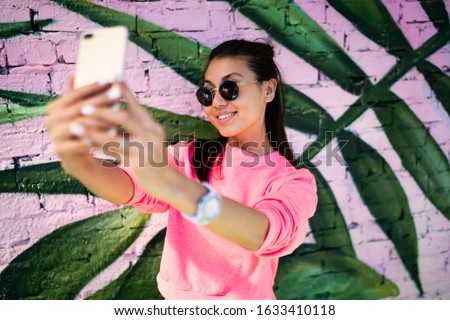 Happy millennial content maker shooting influence video vlog near photo zone enjoying networking lifestyle, cheerful Asian hipster girl in sunglasses smiling at smartphone camera for selfie image