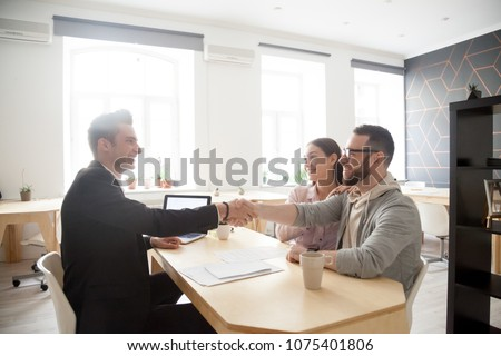 Happy millennial couple and smiling financial advisor, lawyer or realtor shaking hands at office meeting making deal agreement, thanking for help advice, taking loan, buying insurance or services