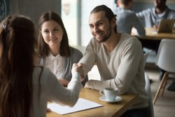 Happy millennial couple handshaking trusted broker signing mortgage contract, satisfied customers and realtor shaking hands making real estate deal, buying insurance or services at meeting in cafe