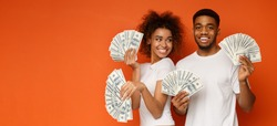 Happy millennial couple posing with lot of money, holding with dollar fans, orange panorama background with empty space