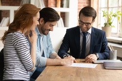 Happy millennial couple signing contract with manager at meeting, excited satisfied clients purchasing first own apartment, making insurance or investment deal, putting signature on document