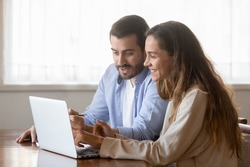 Happy millennial couple sit at table at home browsing web on laptop shopping online together, smiling young husband and wife work on computer at desk pay household bills or taxes in internet banking