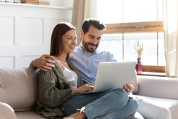 Happy millennial couple sit relax on couch in living room watching video on laptop together, smiling young husband and wife rest on sofa at home browsing Internet using modern computer device