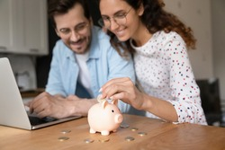 Happy millennial family couple putting coins in piggybank, planning vacation or investments together, saving money for life insurance, managing future expenditures together using computer apps.