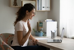 Happy millennial female sitting by laptop pc making video call using device webcam. Friendly young woman teacher tutor start distant lesson from home using conference app waving hand welcoming pupils
