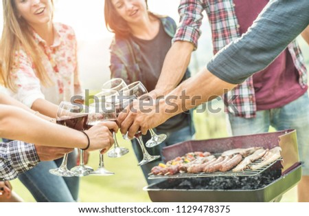 Happy millennial friends cheering with  wine at barbecue outdoor - Adult people having fun drinking wine in vineyard at sunset - Friendship and youth lifestyle - Focus on right bottom hand