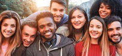 Happy millennial friends from diverse cultures and races having fun posing in front of smartphone camera - Youth and friendship concept - Young multiracial people smiling - Main focus on african man