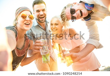 Happy millennial friends group taking selfie at fun beach party drinking cocktails at sunset - Summer joy and friendship concept with young people on vacation - Bright sunshine filtered color tones