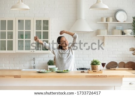 Happy millennial girl preparing healthy breakfast having fun in bright modern kitchen at home, overjoyed young woman cooking in new house or apartment feel excited moving relocating to own dwelling