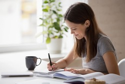Happy millennial girl sit at desk at home studying using textbooks, smiling female student make notes write in notebook prepare for exam or test, do research or assignment, distant education concept