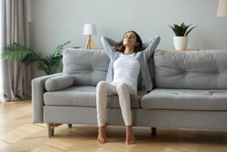 Happy millennial girl sit relax on comfortable couch in living room hands over head, peaceful young woman rest on cozy sofa at home take nap dream with closed breathe fresh air, stress free concept