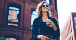 Happy millennial hipster girl in sunglasses laughing on urban setting during sunny day, positive cheerful woman tourist dressed in casual look holding smartphone gadget in hand for communicate