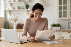 Happy millennial hispanic lady review printed paper documents financial reports satisfied with good state of business low tax rate paid debt confirmation. Glad young female do paperwork read good news
