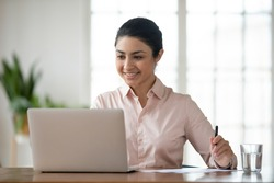 Happy millennial Indian businesswoman sit at desk in office work online on laptop busy with paperwork. Smiling young mixed race female employee worker look at computer screen consult client distant.