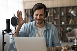 Happy millennial male artist in headphones and guitar have online video music lesson on computer. Smiling young man singer tutor or coach talk greet on webcam digital virtual training at home studio.