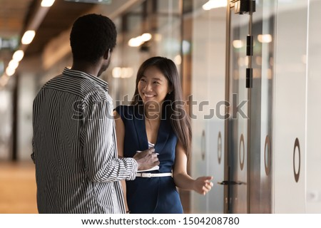 Happy millennial multiethnic employees stand in modern office hallway talking, smiling young diverse ethnic colleagues laugh have fun speaking in corridor, company multiethnic interns chatting