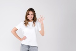 Happy millennial woman looking at camera, showing ok gesture, isolated on white studio background. Smiling female customer agree with good deal, young employee accepting job offer. Empty space