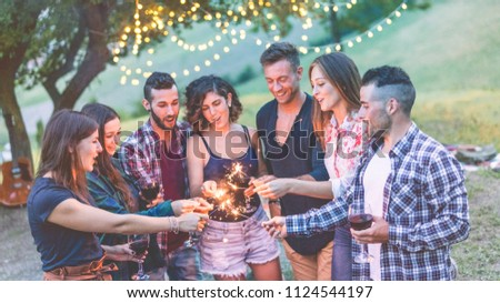 Happy millennials friends having fun at bbq dinner with sparklers lights - Young people celebrating on weekend summer night - Friendship, party and youth concept - Soft focus on fireworks hands