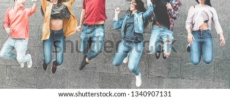 Happy millennials friends jumping outdoor for celebrating - Young people having fun together laughing and smiling - Youth, city lifestyle, team, multiracial, friendship concept - Focus on hands #1340907131