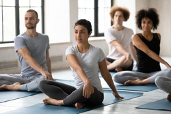 Happy mindful young mixed race people doing simple seated twist exercise, multiethnic diverse beginners practicing Parivrtta Sukhasana barefoot on yoga mat at group class in modern interior.