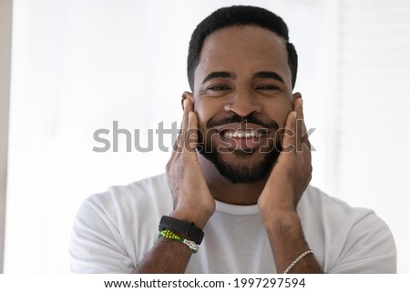 Happy mixed race African man touching soft stubble, stylish beard, smiling at camera. Metrosexual guy satisfied with aftershave balm, moisturizing cream. Male beauty care concept. Head shot portrait Сток-фото ©