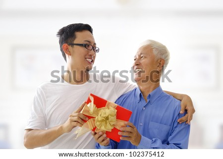 Happy Mixed race Asian father receiving present from his son - stock photo