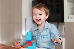 Happy mixed race Asian-German baby boy laughing while playing with plastic blocks toy at home or nursery room.little child having fun learning and play fine motor development.