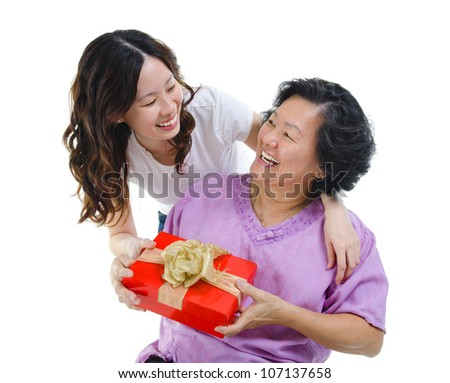 Happy Mixed race Asian mother receiving present from her daughter