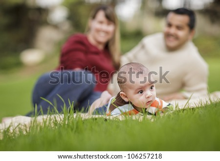 Happy Mixed Race Baby Boy and Parents Playing Outdoors in the Park.
