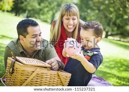 Happy Mixed Race Couple Give Their Son a Piggy Bank at a Picnic in the Park.