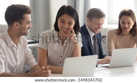 Happy mixed race coworkers sitting at shared table with laptop, working in groups on projects. Happy korean female employee looking at computer screen, talking with young male teammate at office.
