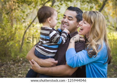 Happy Mixed Race Ethnic Family Having Fun Playing In The Park.
