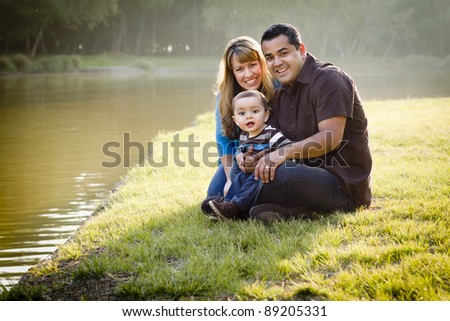 Happy Mixed Race Ethnic Family Posing for A Portrait in the Park by the Lake.