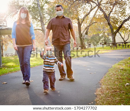 Happy Mixed Race Ethnic Family Walking In The Park Wearing Medical Face Mask.