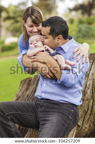 Happy Mixed Race Family Enjoying The Park Together.