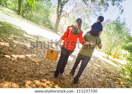 Happy Mixed Race Family with Picnic Basket Enjoy a Walk in the Park.