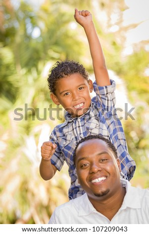 Happy Mixed Race Father and Son Cheering with Fist in the Air at the Park.