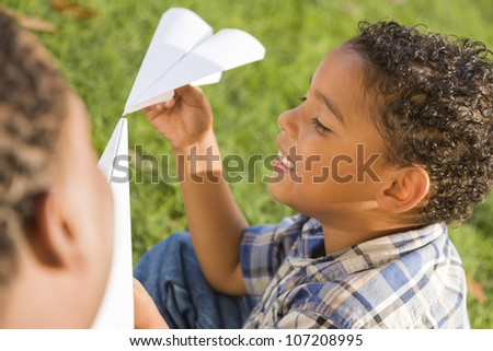 Happy Mixed Race Father and Son Playing with Paper Airplanes in the Park.