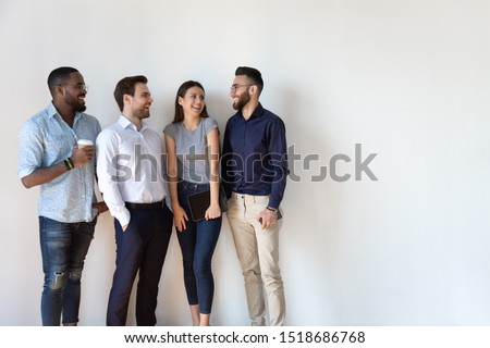 Happy mixed race four employees managers workers standing near wall, having fun. Successful multiethnic business team members corporate staff laughing, enjoying relaxed working atmosphere together.