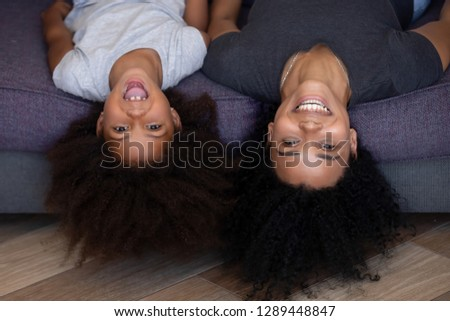 Happy mixed race mother and little daughter laughing lying upside down on sofa looking at camera, black mom and cute funny kid girl with afro hair having fun, african mum and child headshot portrait stock photo