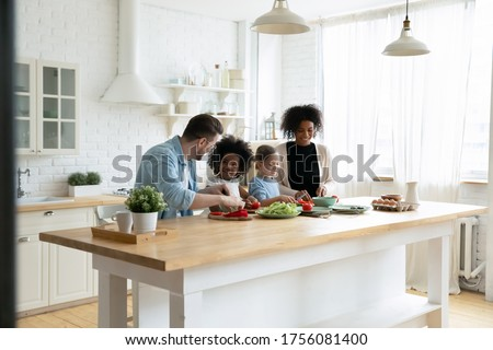 Happy mixed race multinational family with daughters prepare vegetable organic fresh salad, enjoy pastime cooking process in cozy kitchen, healthy eating, parents teach kids, weekend at home activity